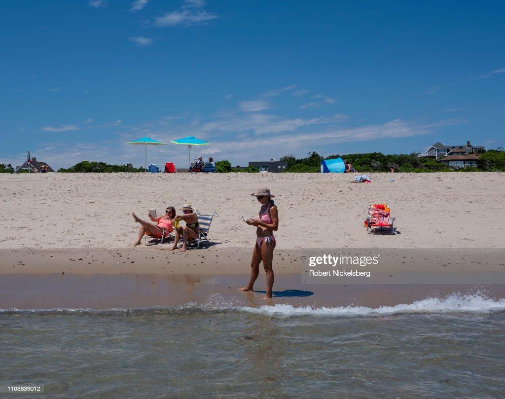 Vacationers read along Cape Cod and Atlantic Ocean shoreline in East