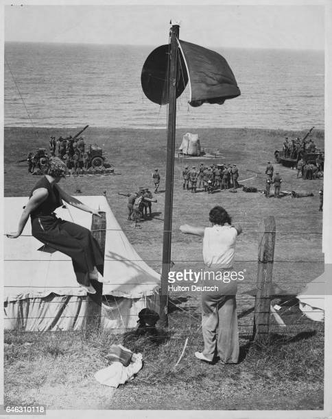Vacationers watch as the 1st Antiaircraft Brigade performs training exercises along the Somerset coast