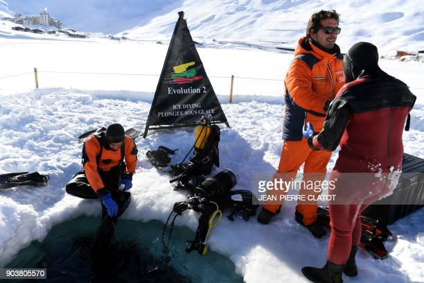 Vacationers wearing special equipment exit a hole after ice diving at minus two degrees Celsius in the frozen lake of Val Claret in the French Alps...