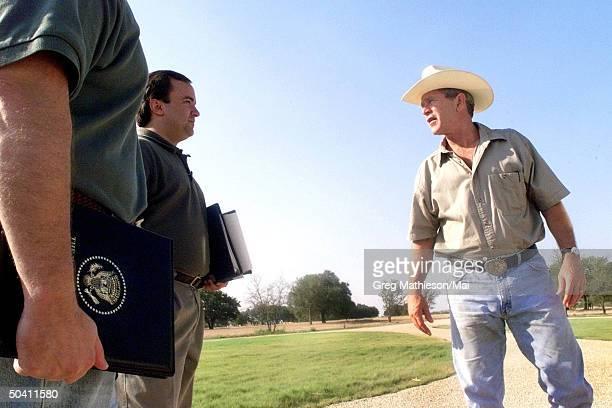 Vacationing President George W Bush talking w senior staff members Steve Biegun and press secretary Scott McClellan at the Bush Ranch