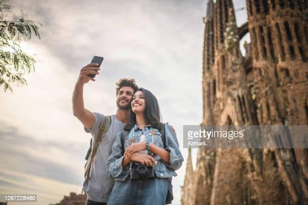 urlaub junges paar macht selfie bei sagrada familia - familia stock-fotos und bilder