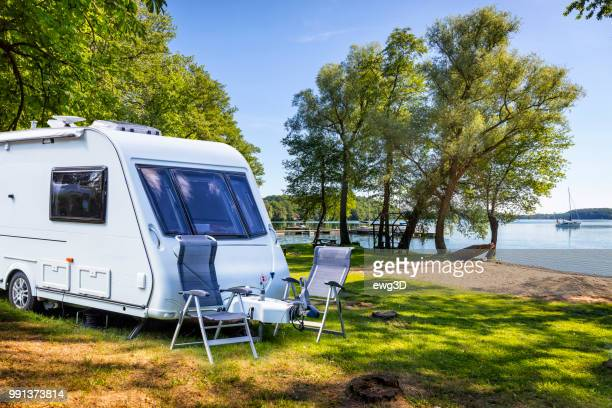 vacations in poland - camper trailer on the shore of bay of the drawsko lake - camper trailer stock pictures, royalty-free photos & images