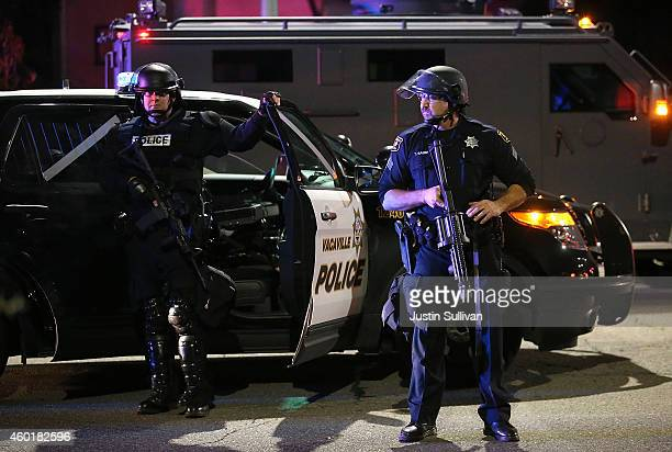 Vacaville California police officer stands with an automatic weapon and full riot gear as he monitors a demonstration over recent grand jury...