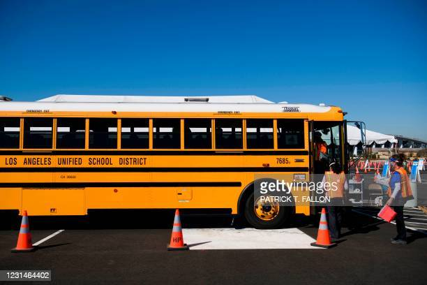 Vaccination site workers board a school bus transporting education workers as it arrives at a mass vaccination site in a parking lot at Hollywood...