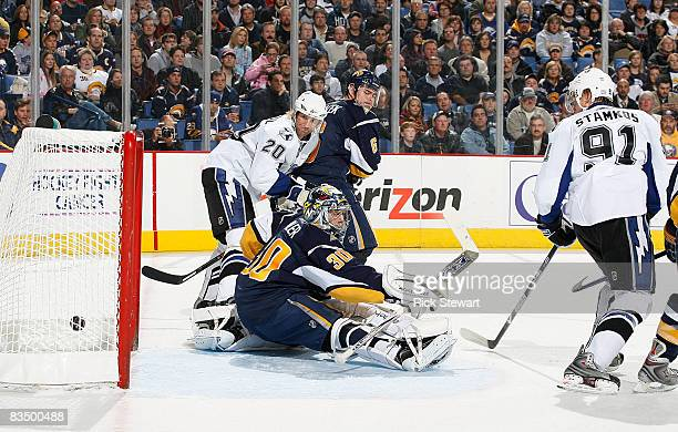 Vaclav Prospal and Steve Stamkos of the Tampa Bay Lightning watch Stamkos' shot go into the goal his first in the NHL past Ryan Miller and Jaroslav...