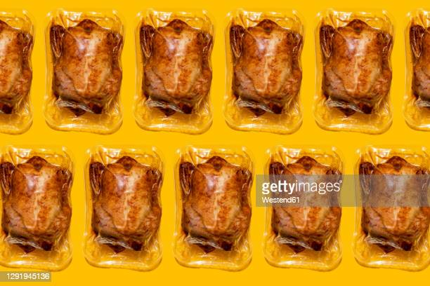 vacuum packed roasted chickens on yellow background - packaging stock pictures, royalty-free photos & images