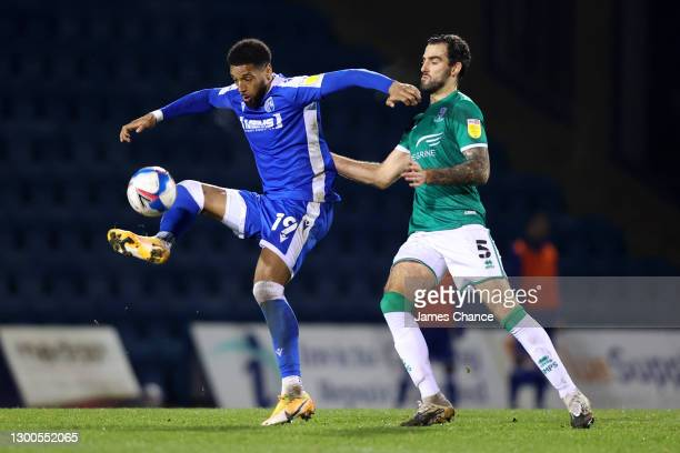 Vadaine Oliver of Gillingham FC battles for possession with Adam Jackson of Lincoln City during the Sky Bet League One match between Gillingham and...
