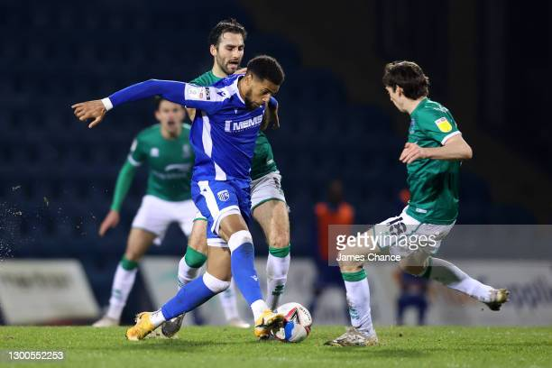 Vadaine Oliver of Gillingham FC is challenged by Adam Jackson and Conor McGrandles of Lincoln City during the Sky Bet League One match between...