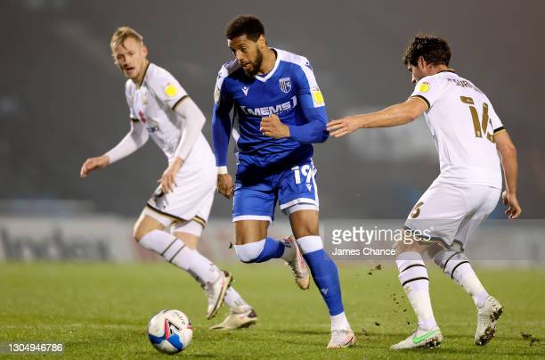 Vadaine Oliver of Gillingham FC is challenged by Andrew Surman of Milton Keynes Dons during the Sky Bet League One match between Gillingham and...