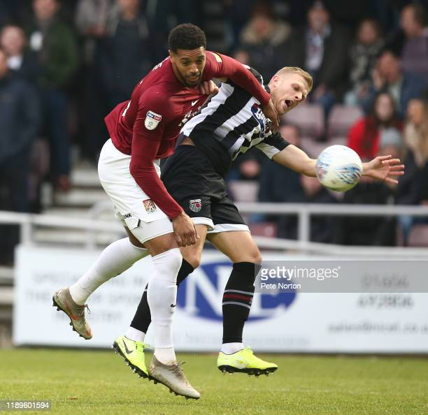 Vadaine Oliver of Northampton Town contests the ball with Harry Davis of Grimsby Town during the Sky Bet League Two match between Northampton Town...