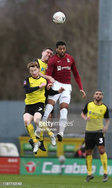 Vadaine Oliver of Northampton Town contests the ball with Jake Buxton and Stephen Quinn of Burton Albion during the FA Cup Third Round match between...