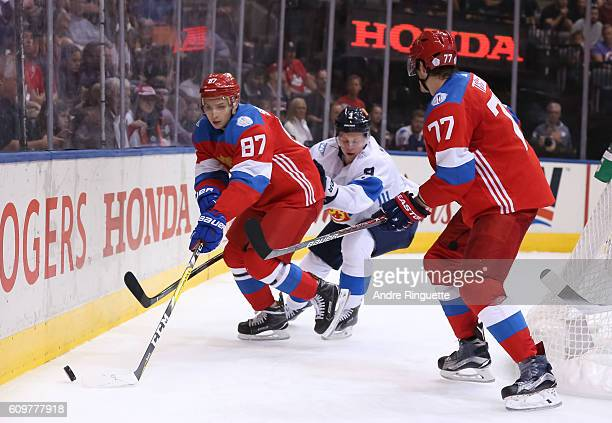 Vadim Shipachev and Ivan Telegin of Team Russia battle for the puck with Olli Maatta of Team Finland during the World Cup of Hockey 2016 at Air...