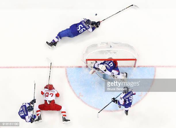 Vadim Shipachyov of Olympic Athlete from Russia and Michal Cajkovsky of Slovakia fall to the ice in the first period during the Men's Ice Hockey...