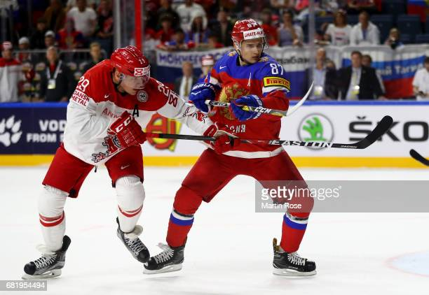 Vadim Shipachyov of Russia challenges Morten Madsen of Denmark for the puck during the 2017 IIHF Ice Hockey World Championship game between Russia...