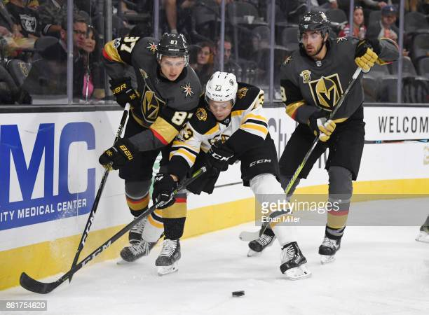 Vadim Shipachyov of the Vegas Golden Knights and Charlie McAvoy of the Boston Bruins battle for the puck behind the net as Alex Tuch of the Knights...