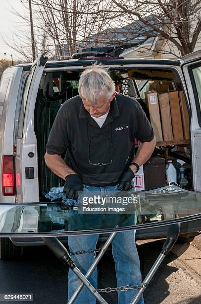 Vadnais Heights Minnesota A small business mobile glass service owner installing a new windshield on a new car Preparing the windshield for...
