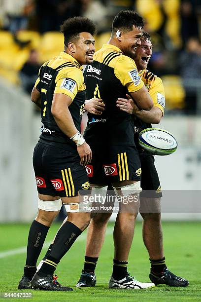 Vaea Fifita of the Hurricanes is congratulated on his try by teammates Ardie Savea and Reggie Goodes during the round 15 Super Rugby match between...