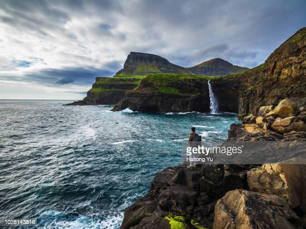 vagar, faroe islands. backpacker looking at mulafossur waterfall. - islas faroe fotografías e imágenes de stock