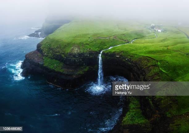 vagar, faroe islands. mulafossur waterfall. high angle aerial shot. - 漂白した ストックフォトと画像