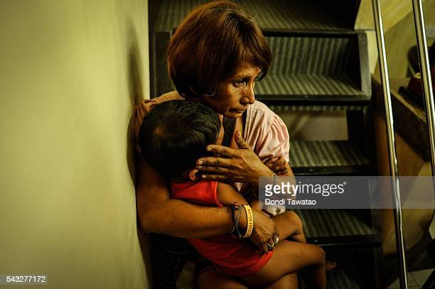 A vagrant with a boy sit at a police station after being picked up during curfew on June 8 2016 in Manila Philippines The presidentelect of the...