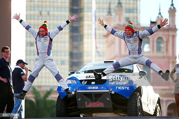 Vaidotas Zala of Lithuania and SEAT Bee Dakar and his codriver Saulius Jurgelenas of Lithuania jump in front of their Leon Seat car on the podium...