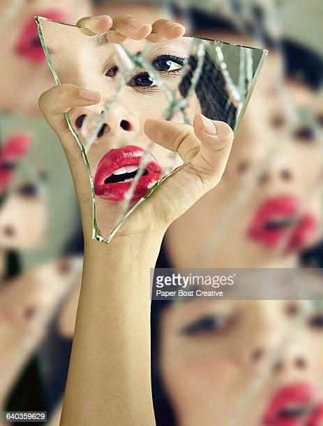 Vain woman checking her lipstick in broken glass