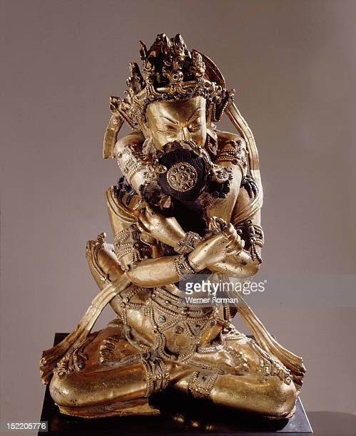 Vajrasattva also known as Vajradhara the Supreme Buddha identified by his hands which are held in the Vajrahumkara mudra a thunderbolt in each sits...