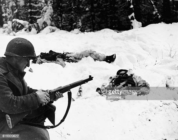 Vakasin loads his rifle. The two dead Germans have on camouflage snow suits.