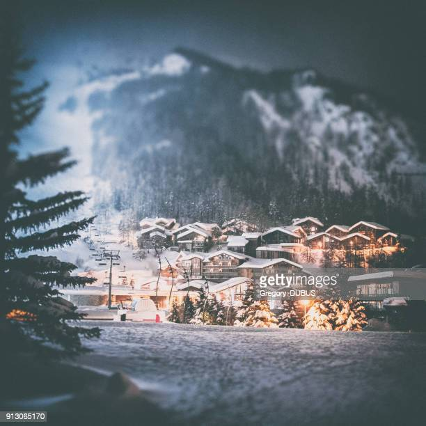 val d'isere french ski resort illuminated village by snowy night in european alps in winter - village stock pictures, royalty-free photos & images