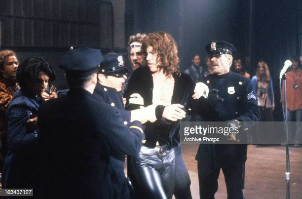 Val Kilmer being apprehended by the police in a scene from the film 'The Doors', 1991.
