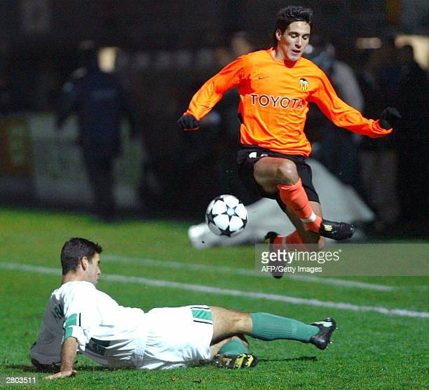 Valence CG's Ropdriguez Vicente jumps over a tackle by Maccabi Haifa's Eitan Azaria during their second leg UEFA cup match, 11 December 2003 in...
