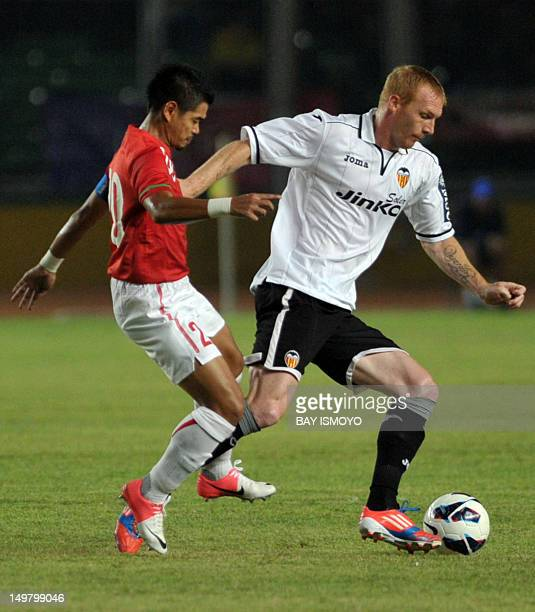 Valencia CF's Jeremy Mathieu vies for the ball with Indonesia's Bambang Pamungkas during a friendly football match between Spain's Valencia CF and...
