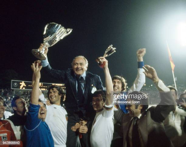 Valencia coach Alfredo Di Stefano holding the trophy aloft as he celebrates with his players after the UEFA European Cup Winners' Cup Final between...