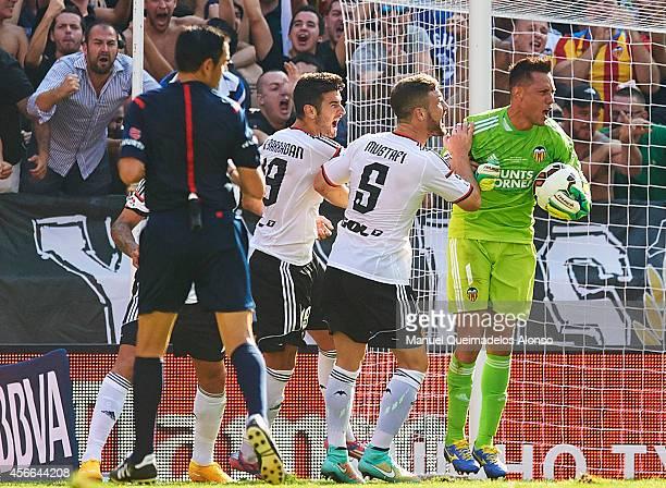 Valencia goalkeeper Diego Alves celebrates with his teammates Shkodran Mustafi and Antonio Barragan after saving a penalty during the La Liga match...