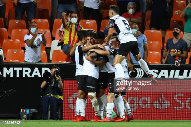 Valencia players celebrate the opening goal scored by Valencia's Spanish forward Hugo Duro during the Spanish League football match between Valencia...