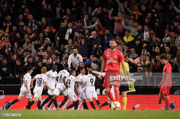 Valencia players gather to celebrate the opening goal during the Spanish league football match between Valencia CF and Real Madrid CF at the Mestalla...