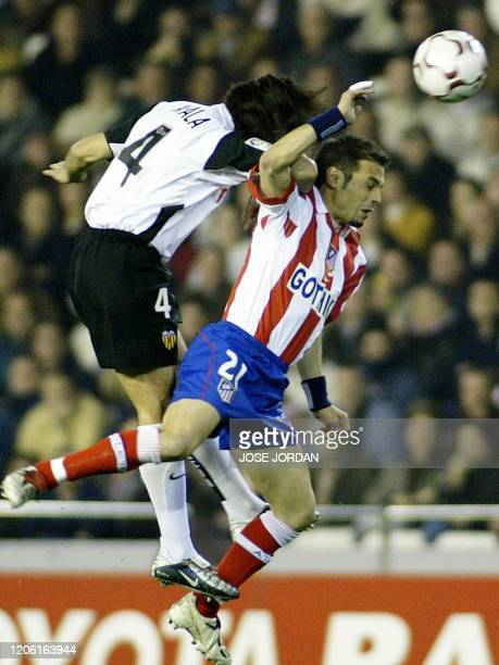 Valencia 's Argentinian Fabian Ayala jumps for the ball with Atletico Madrid's Greeck Themistoklis Nikoladis during a Premier league match between...