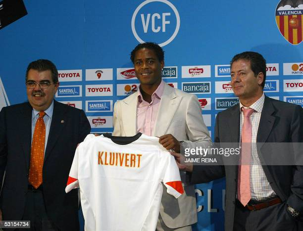 Dutch player Patrick Kluivert shows his Valencia T-shirt next to the club's president Juan Bautista Soler and Sport director Javier Subirats during...
