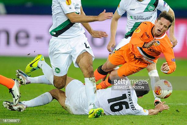 Valencia's Agentinian forward Pablo Piatti is tackled by St Gallen's Swiss midfielder Mathias Vitkieviez during the UEFA Europa League Group A...