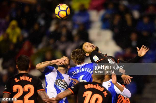 Valencia's Argentinian defender Ezequiel Garay jumps for the ball with Deportivo La Coruna's Spanish defender Raul Albentosa and Deportivo La...