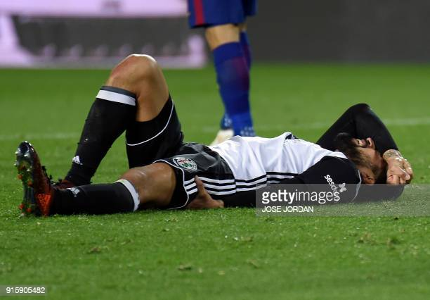 Valencia's Argentinian defender Ezequiel Garay lies on the field after resulting injured during the Spanish 'Copa del Rey' second leg semifinal...