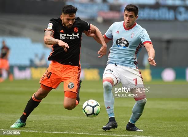 Valencia's Argentinian defender Ezequiel Garay vies with Celta Vigo's Uruguayan forward Maxi Gomez during the Spanish league football match between...