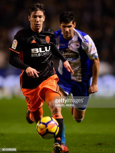 Valencia's Argentinian forward Luciano Vietto runs for the ball with Deportivo La Coruna's Spanish defender Juanfran Moreno during the Spanish league...
