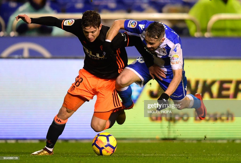 Valencia's Argentinian forward Luciano Vietto (L) vies with Deportivo La Coruna's Portuguese defender Luisinho during the Spanish league football match between RC Deportivo de la Coruna and Valencia CF at the Municipal de Riazor stadium in La Coruna on January 13, 2018. /