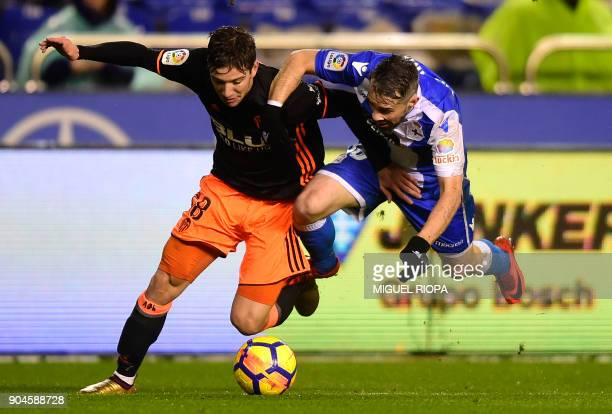 Valencia's Argentinian forward Luciano Vietto vies with Deportivo La Coruna's Portuguese defender Luisinho during the Spanish league football match...