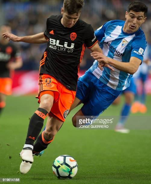Valencia's Argentinian forward Luciano Vietto vies with Malaga's Spanish defender Diego Gonzalez during the Spanish league football match between...