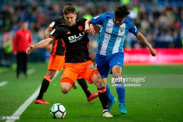 Valencia's Argentinian forward Luciano Vietto vies with Malaga's Argentinian midfielder Gonzalo Castro 'Chory' during the Spanish league football...