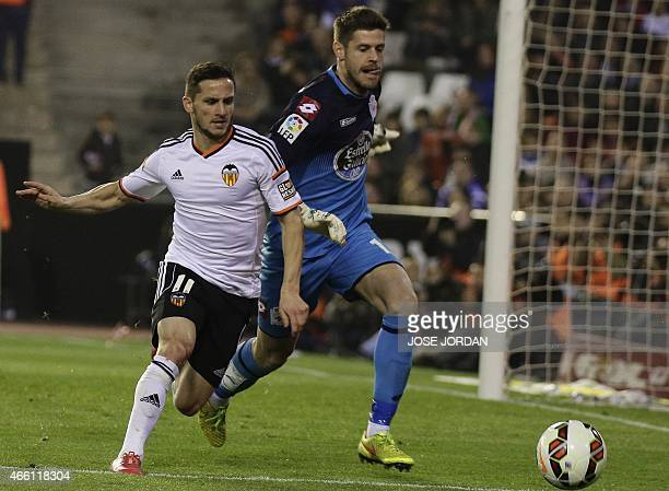 Valencia's Argentinian forward Pablo Piatti vies with Deportivo's goalkeeper Fabri during the Spanish league football match Valencia CF vs RC...