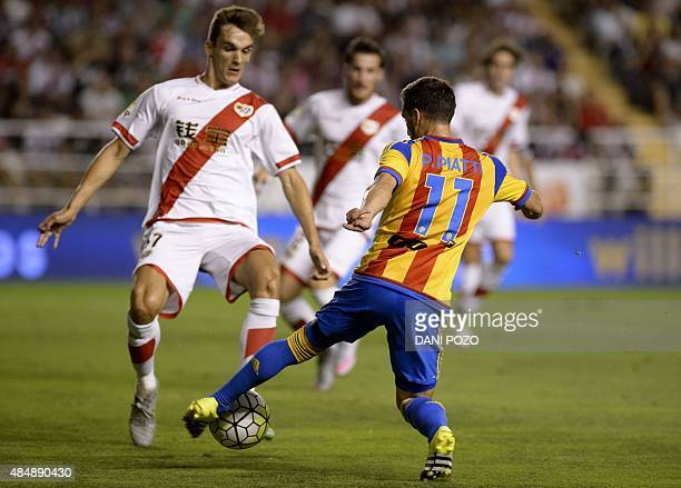 Valencia's Argentinian forward Pablo Piatti vies with Rayo's defender Diego Llorente during the Spanish league football match Rayo Vallecano de...