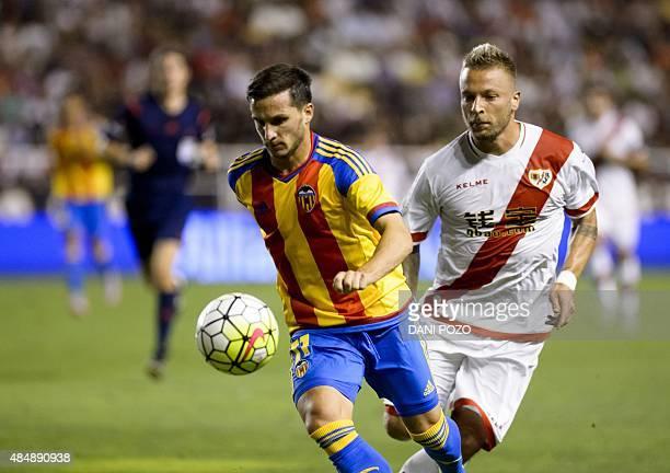 Valencia's Argentinian forward Pablo Piatti vies with Rayo's German forward Patrick Ebert during the Spanish league football match Rayo Vallecano de...
